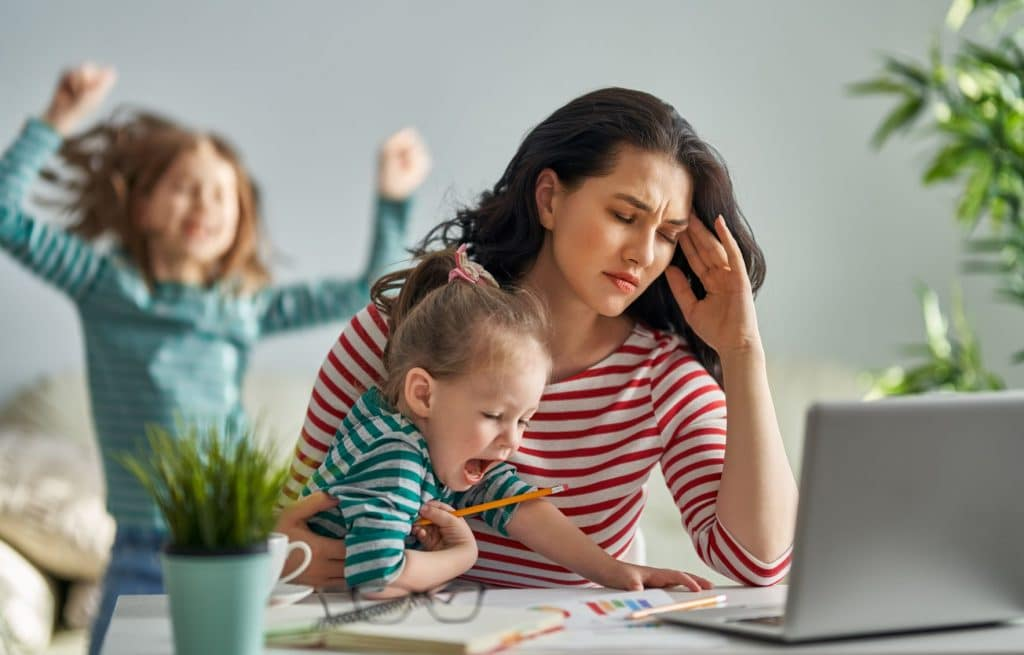 woman stressed with kids working at home