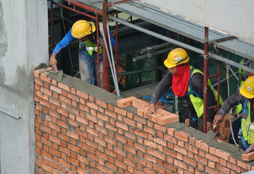 2 bricklayers working on a platform